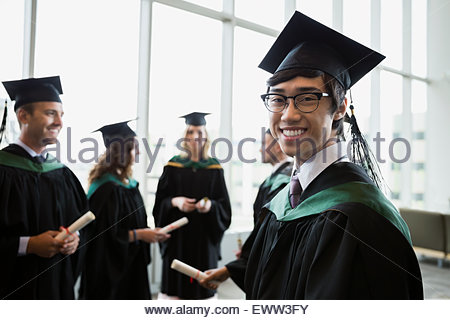 Portrait confident college graduate in cap and gown - Stock Photo
