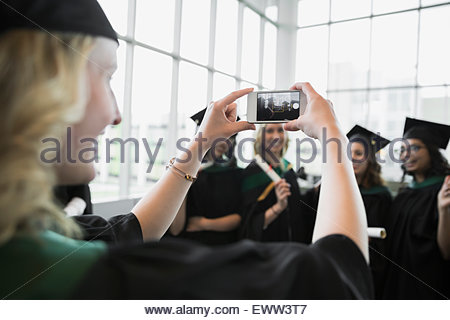 College graduates in cap and gown posing photograph - Stock Photo