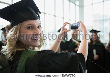 Portrait smiling college graduate photographing friends - Stock Photo