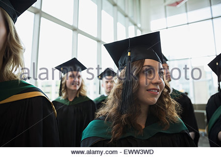 Smiling college graduate in cap and gown - Stock Photo