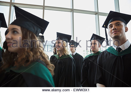Smiling college graduates in cap and gown - Stock Photo