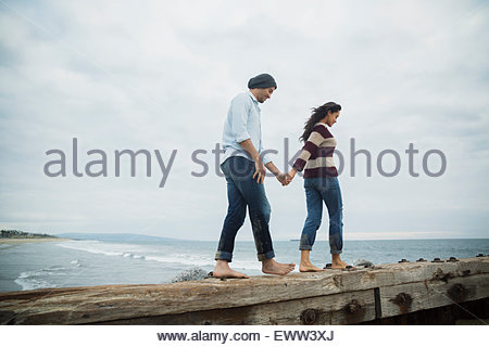 Barefoot couple holding hands walking along ocean jetty - Stock Photo