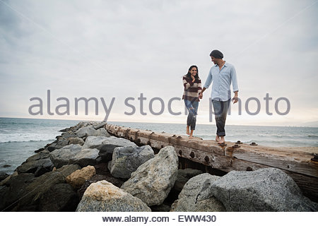 Couple holding hands walking along ocean jetty - Stock Photo