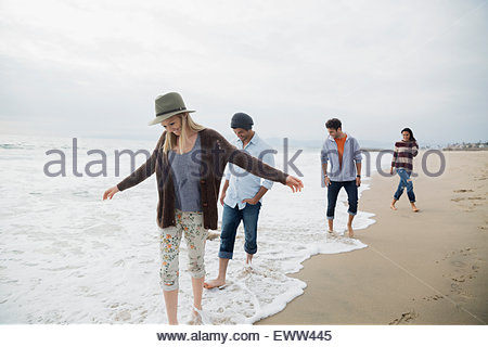 Friends wading in ocean surf on beach - Stock Photo