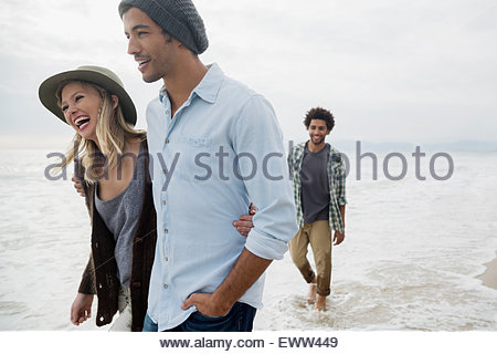 Smiling couple walking in ocean surf - Stock Photo