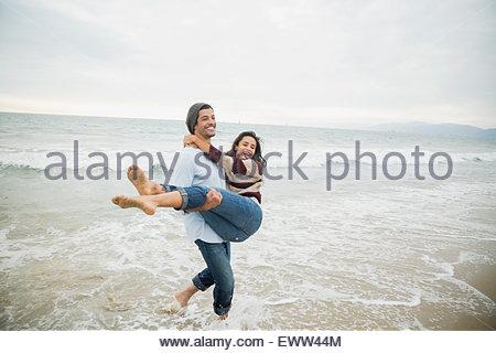 Playful boyfriend carrying girlfriend in ocean surf - Stock Photo