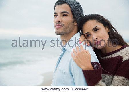 Pensive brunette couple looking at ocean - Stock Photo