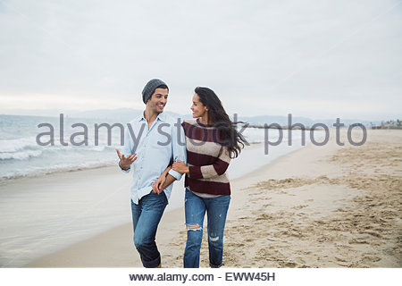 Couple walking and talking on beach - Stock Photo