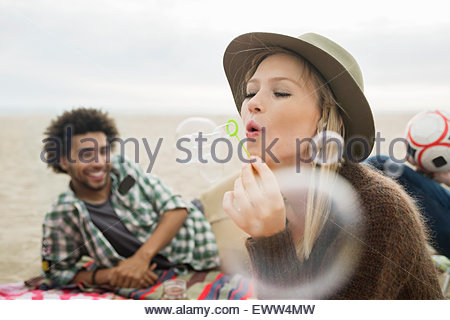 Woman blowing bubbles on beach - Stock Photo