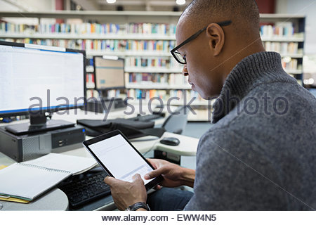 College student studying with digital tablet in library - Stock Photo