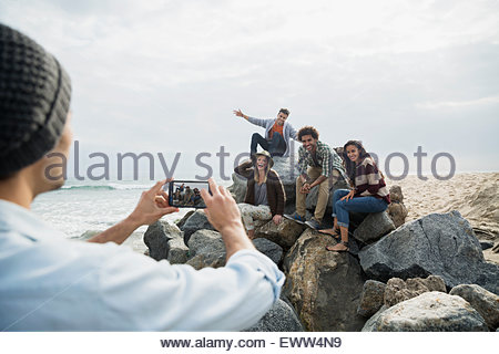Friends posing for photograph on beach rocks - Stock Photo