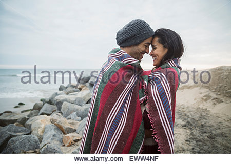 Affectionate couple wrapped blanket face to face beach - Stock Photo