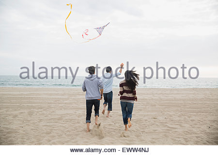 Friends running and flying a kite on beach - Stock Photo
