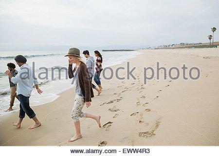 Friends walking toward ocean on beach - Stock Photo