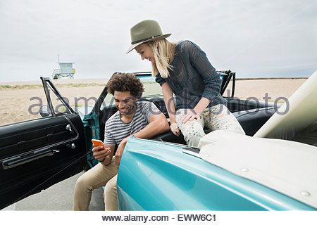 Young couple in convertible texting cell phone beach - Stock Photo