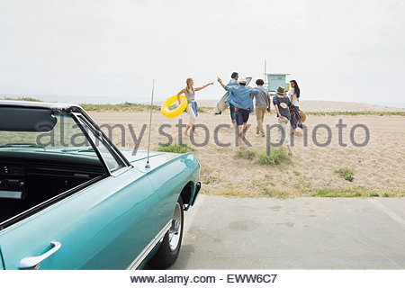 Enthusiastic friends running from convertible onto beach - Stock Photo