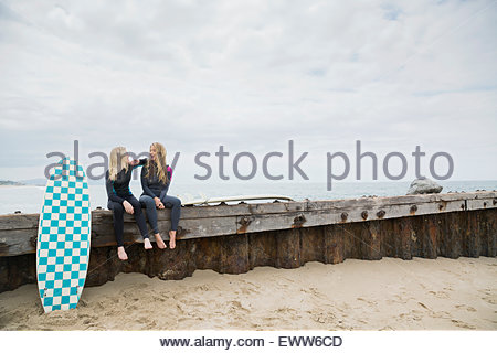 Female surfers with surfboards on beach jetty - Stock Photo
