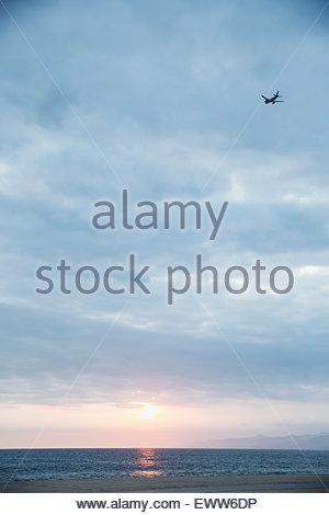 Plane in overcast sunset sky over ocean - Stock Photo