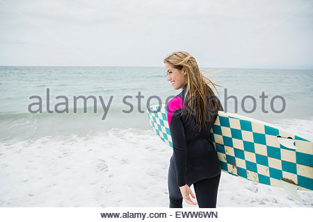 Blonde female surfer carrying surfboard into ocean - Stock Photo