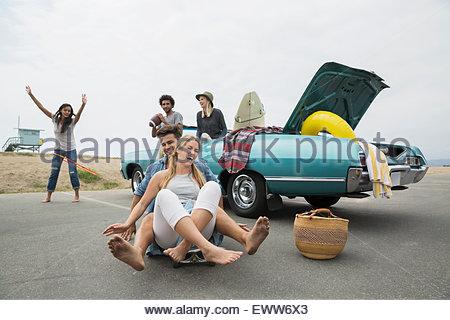 Young couple riding skateboard near convertible at beach - Stock Photo
