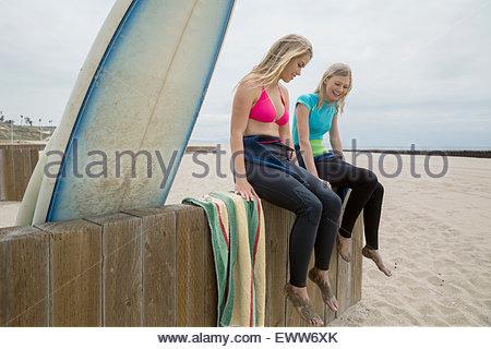 Female surfers taking a break on beach wall - Stock Photo