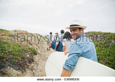 Portrait smiling young man carrying surfboard beach path - Stock Photo