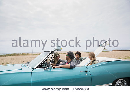 Young couples riding in convertible with surfboard beach - Stock Photo