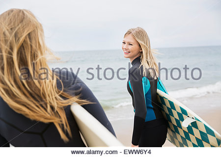 Blonde female surfers with surfboards on beach - Stock Photo