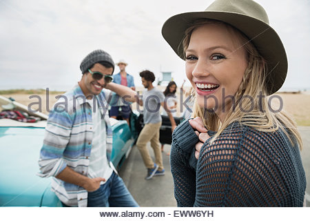Portrait smiling young woman hanging out friends beach - Stock Photo