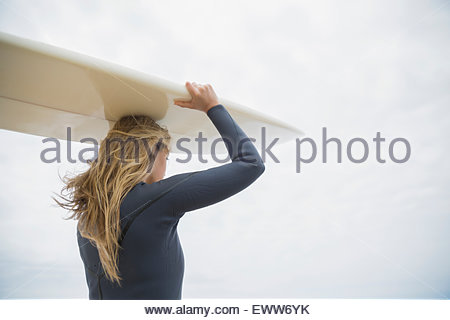 Blonde female surfer carrying surfboard overhead - Stock Photo
