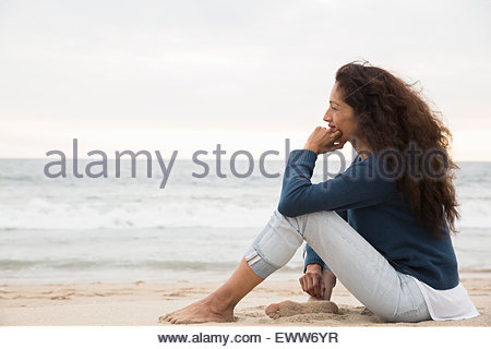 Pensive woman sitting on beach looking at view - Stock Photo