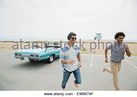 Friends running from beach and convertible parking lot - Stock Photo