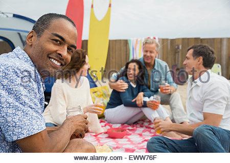 Friends enjoying beach picnic - Stock Photo
