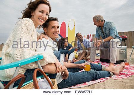 Portrait couple enjoying beach picnic with friends - Stock Photo