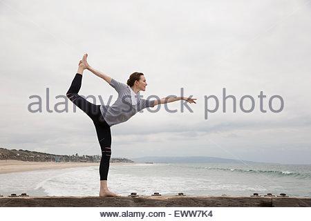 Woman doing yoga king dancer pose on beach - Stock Photo