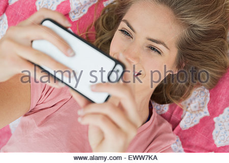 Blonde woman laying on blanket and taking selfie - Stock Photo