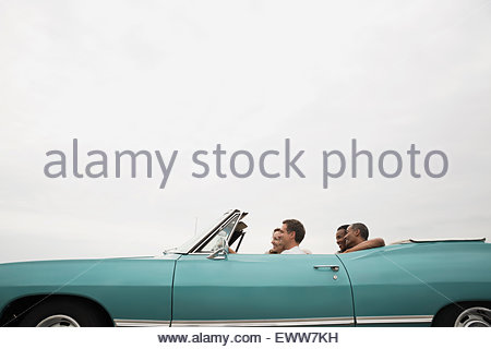 Couples riding in convertible under overcast sky - Stock Photo
