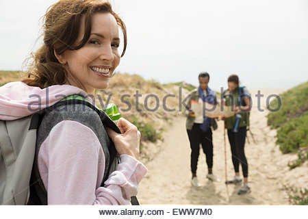 Portrait smiling woman with backpack hiking with friends - Stock Photo