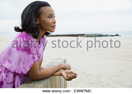 Pensive woman looking at view on beach - Stock Photo