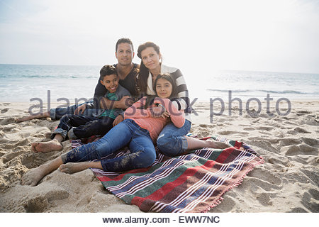 Portrait family relaxing on blanket on sunny beach - Stock Photo