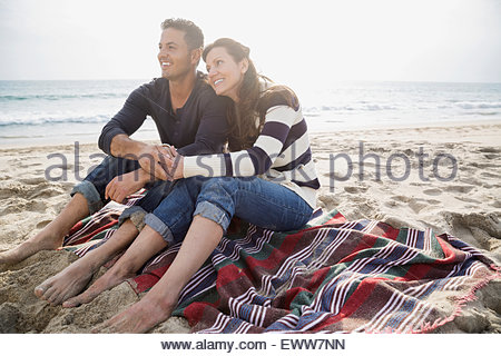 Affectionate couple relaxing on blanket on sunny beach - Stock Photo