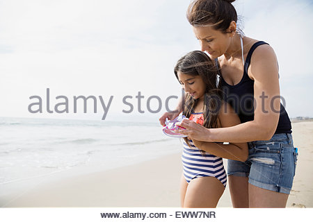 Mother helping daughter with goggles on beach - Stock Photo
