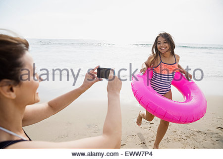 Mother photographing daughter inflatable ring camera phone beach - Stock Photo
