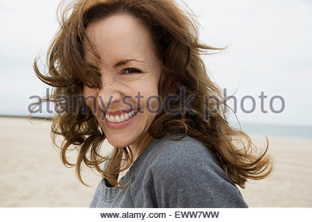 Portrait enthusiastic brunette woman at beach - Stock Photo