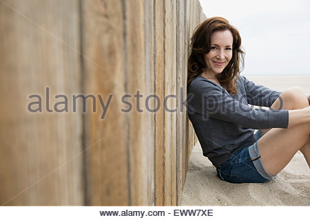 Portrait smiling brunette woman sitting at beach wall - Stock Photo