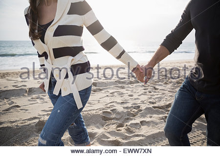 Couple holding hands and walking on beach - Stock Photo