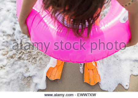 Girl in inflatable ring and flippers ocean surf - Stock Photo