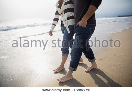 Barefoot couple walking on sunny beach - Stock Photo