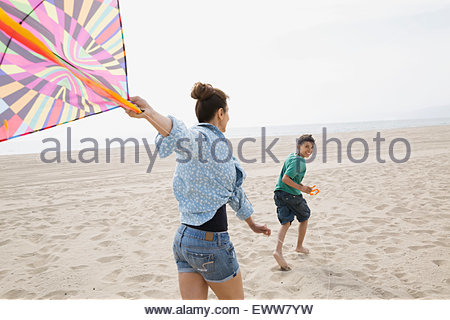 Mother and son flying kite at beach - Stock Photo