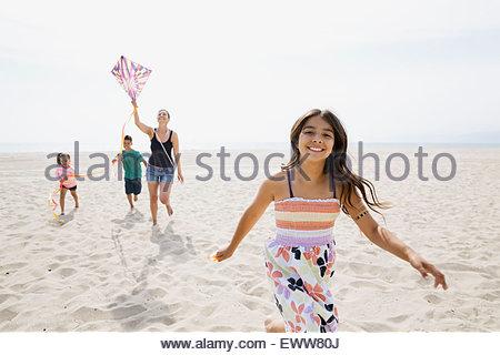 Portrait family flying kite on sunny beach - Stock Photo